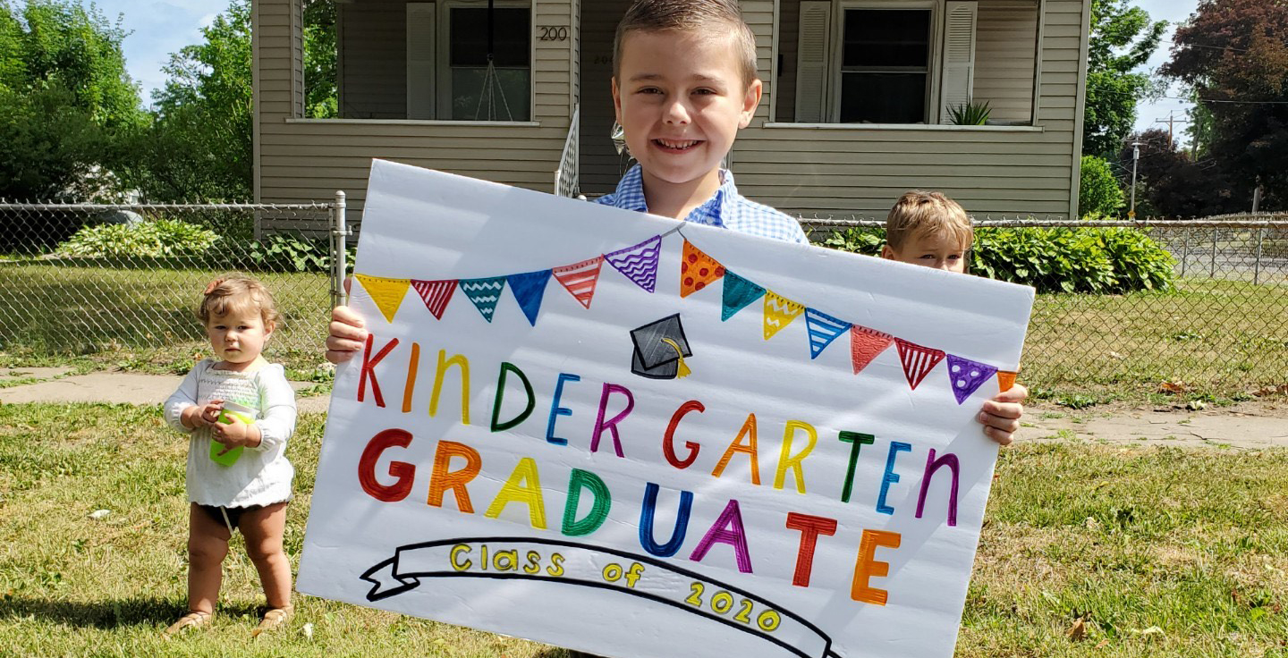 UAS Scholar smiles with Kindergarten Graduation Sign