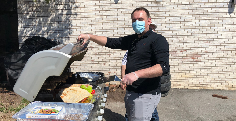 Utica Academy of Science elementary school teachers and staff working during Spring Recess fire up the grill on a sunny day for a BBQ cookout.