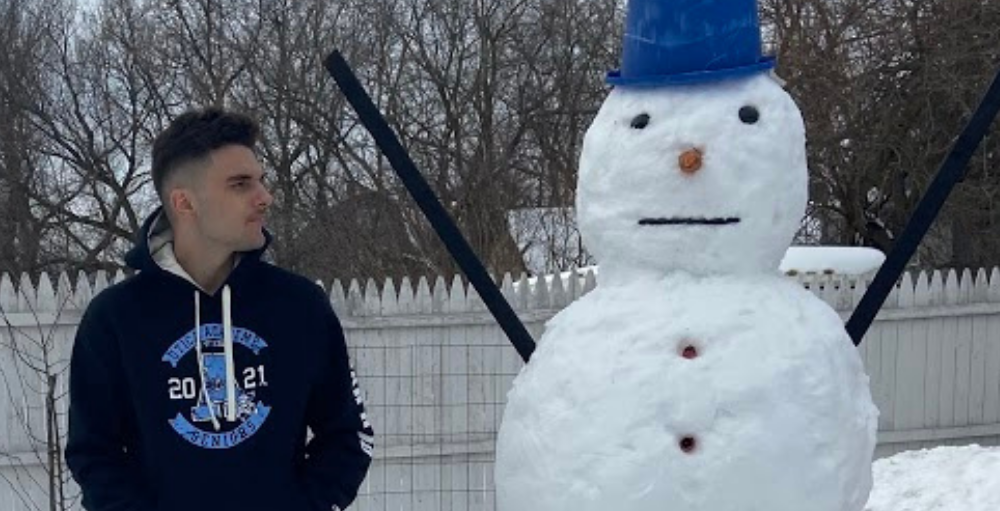 Amar Halimanovic, 1st place winner, poses next to his snowman he built for the Utica Academy of Science National Honors Society's first-ever Snowman Building Contest.
